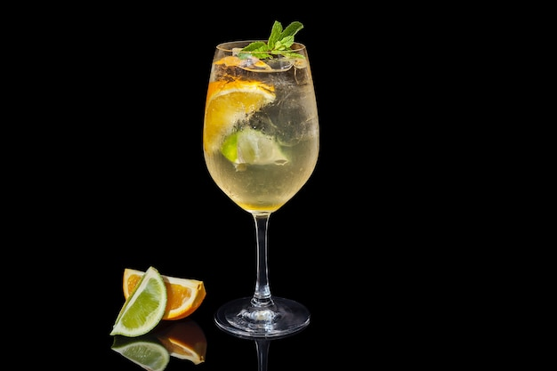 Алкогольный апельсиновый сок на черном фоне, украшенный долькой апельсина и мятой. алкогольный апельсиновый сок на черном фоне.