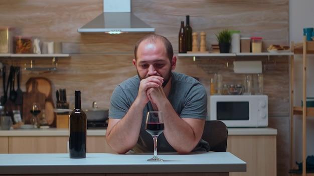 控えようとしている頭痛のあるアルコール依存症の人。片頭痛、うつ病、病気、不安感に苦しんでいる不幸な人は、アルコール依存症の問題を抱えているめまいの症状で疲れ果てています。