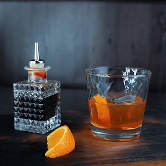 오렌지 조각과 함께 알코올성 달콤한 과일 시럽은 갈색 음료와 함께 크리스탈 병 옆에있는 바의 나무 테이블에 선다. 나이트 클럽에서의 주말