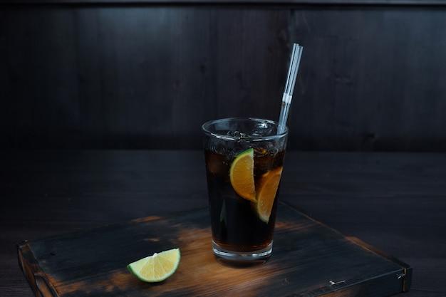 얼음, 위스키 및 코카콜라가 추가 된 알코올성 맛있는 칵테일, 라임 조각이 레스토랑의 나무 테이블 위에 서 있습니다. 바에서 원래 제공되는 음료.