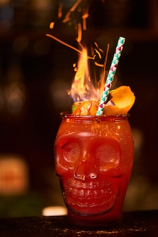 Alcoholic zombie cocktail consisting of absinthe, homemade spiced rum, cranberry and grapefruit juice in a glass skull-shaped