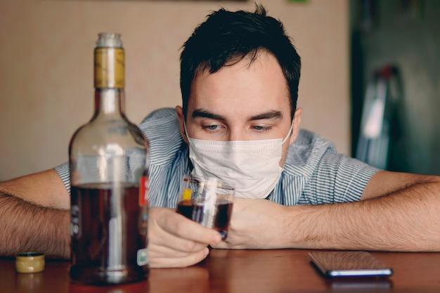 アルコール依存症、アルコール依存症、人々の概念-自宅でラム酒のボトルを持った男性のアルコール依存症。退屈で一人で酔った失業者の専門家は、自己隔離で隔離されます。