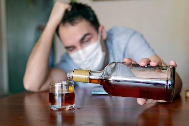 Алкоголизм, наркомания и люди понятие - мужчина-алкоголик с бутылкой рома дома. безработный специалист, напившийся от скуки в одиночестве, находится на карантине в самоизоляции.