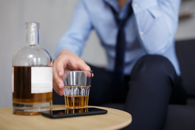 Alcoholism, business and stress concept - close up of whiskey bottle and glass in businessman hand