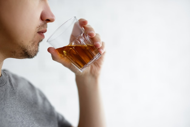 Alcoholism concept - close up of young man drinking whiskey over white background with copy space