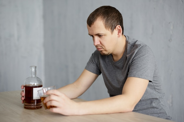 Alcoholism and depression concept - unhappy young man sitting with glass and bottle of whiskey at home or pub