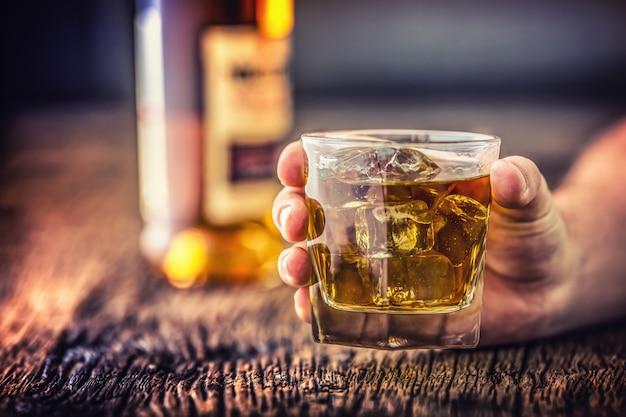 알코올 중독.손으로 알코올을 섭취하고 증류된 위스키 브랜디 또는 코냑을 마십니다.
