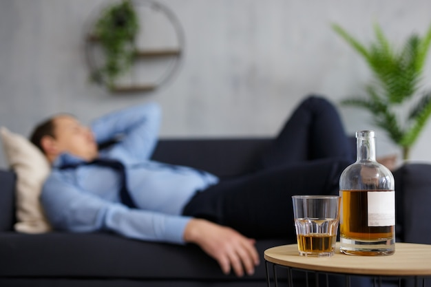 Alcoholism, stress and business concept - close up of whiskey bottle and glass on the table and sleeping drunk businessman