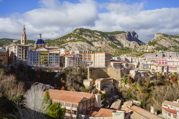 Алькой, испания. промышленный город с горами позади