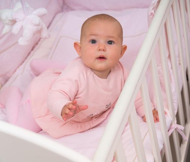 クローズアップの肖像画で不思議にカメラを見上げているベビーベッドの好奇心旺盛な小さな女の赤ちゃんに警告