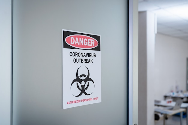 Alert notice paper on the door of danger coronavirus outbreak with biohazard symbol and authorized personnel only