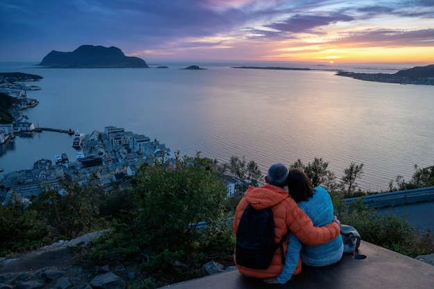 Старшие пары сидя на стенде смотря городской пейзаж на заходе солнца, alesund, больше og romsdal, норвегии.