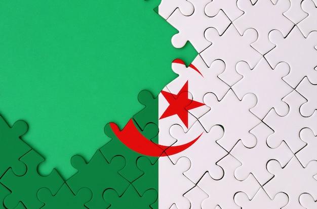 알제리 국기는 왼쪽에 무료 녹색 복사 공간이있는 완성 된 직소 퍼즐에 그려져 있습니다.