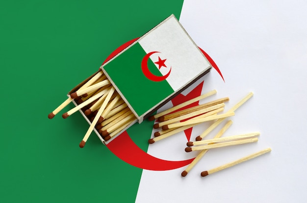 Algeria flag  is shown on an open matchbox, from which several matches fall and lies on a large flag