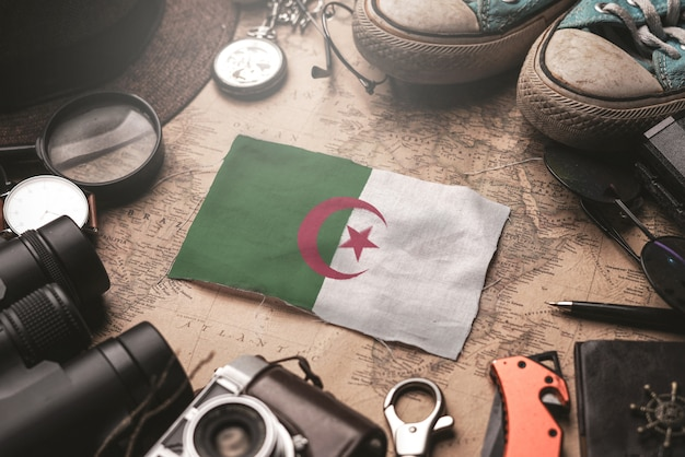 Algeria flag between traveler's accessories on old vintage map. tourist destination concept.