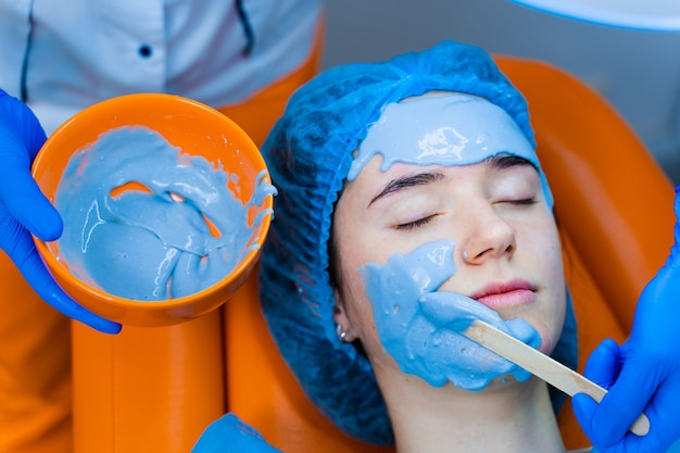 Alginate moisturizing mask for face and skin of young girl. spa procedure for rejuvenation. beautician smears blue mask. dermatology in medical clinic