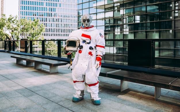 미래의 역에서 외계인 우주인입니다. 도시 지역을 걷고 있는 우주복을 입은 우주 비행사