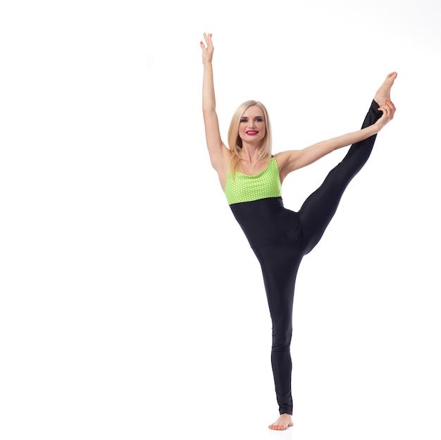 균형 잡기에 관한 모든 것. 카메라 절연 copyspace 스포츠 피트니스 운동 개념에 미소 한 발에 균형을 그녀의 다리를 뻗어 매력적인 여성 체조