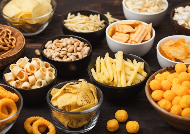 All classic potato snacks with peanuts, popcorn and onion rings and salted pretzels in bowl plates on wood. twirls with sticks and potato chips and crisps with nachos and cheese balls.