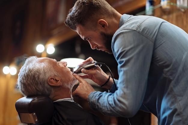 すべての詳細。シニア理髪店クライアントの若いハンサムなひげを生やした美容師トリミングひげの側面図。