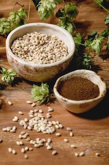 Все для заваривания. свежие зеленые шишки хмеля, зерна пшеницы и красный ферментированный солод в керамических мисках над деревянным столом.