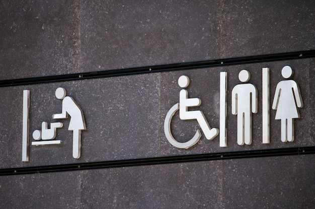 All genders and disabled toilet sign, changing room sign, minimal sign design on grey wall, selective focus