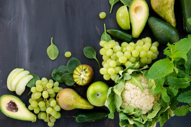 すべての緑の野菜と果物の暗い背景
