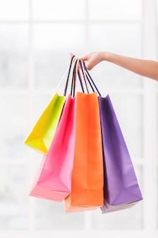 내가 판매하는 모든 것. 멀티 컬러 쇼핑백을 들고 여성 손의 클로즈업