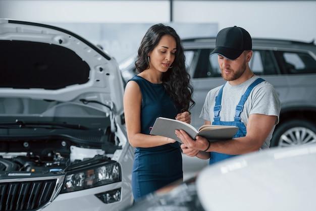 私がやったすべて。修理された車を取り戻す青い制服を着た従業員とオートサロンの女性