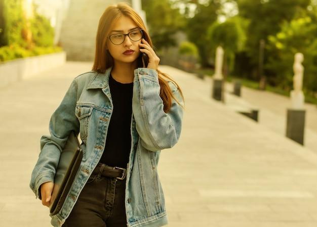Все в бизнесе. молодая стильная женщина в джинсовой куртке и очках держит ноутбук и разговаривает по телефону во время прогулки по городу.