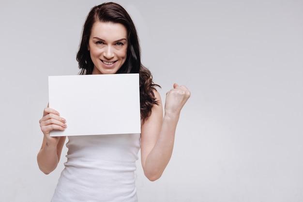 Все в наших руках. уверенная независимая мотивирующая дама сжимает кулак и принимает мощную позу с белым знаком