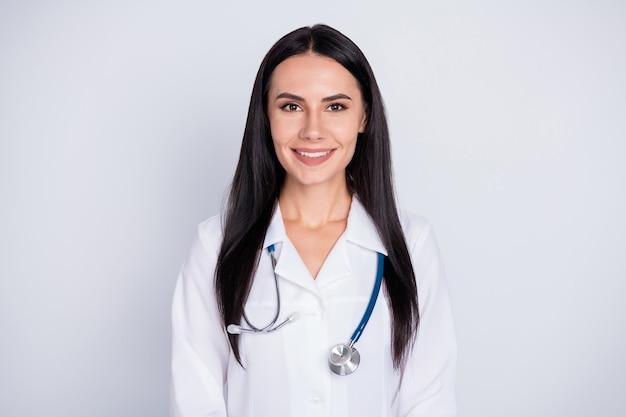 Все хорошо фото привлекательной женщины практикующего врача хорошего настроения, дружелюбно улыбающейся пациентам, носящих белый лабораторный халат, стетоскоп, изолированный серый цвет фона