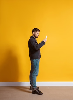 All the life in gadget. young caucasian man using smartphone, serfing, chatting, betting. full length portrait isolated on yellow wall. concept of modern technologies, millennials, social media.