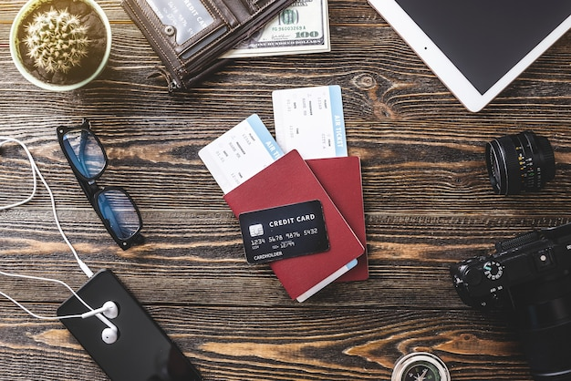 All the necessary things for the flight on vacation. plane tickets, passport, phone and credit card on a wooden background