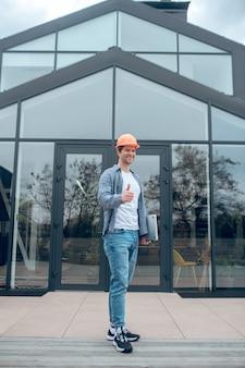 모두 완벽합니다. 야외 건물의 유리 벽 배경에 대해 확인 제스처를 보여주는 노트북과 함께 안전 헬멧에 즐거운 잘 생긴 젊은 남자