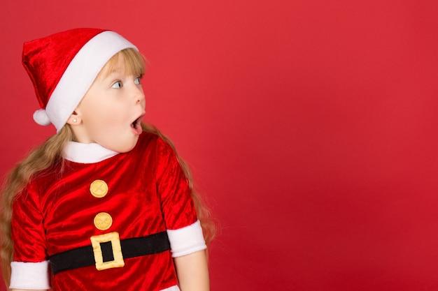 이 모든 것이 나를 위해! 멀리 찾고 크리스마스 모자와 산타 옷을 입고 귀여운 소녀의 프로필은 측면에 그녀의 입을 열고 copyspace 충격