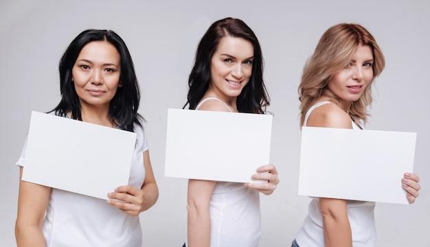 Все вместе. милые милые разные дамы держат листы бумаги, улыбаясь и позируя