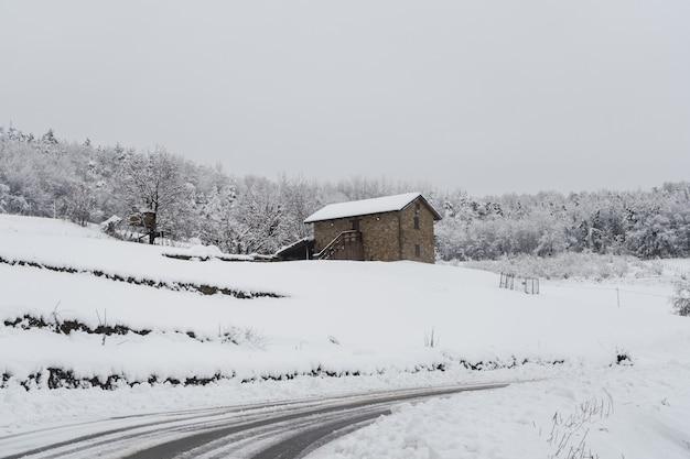 イタリア北部の雪と霧に覆われた真っ白な風景。雪に覆われた素朴な石造りの家