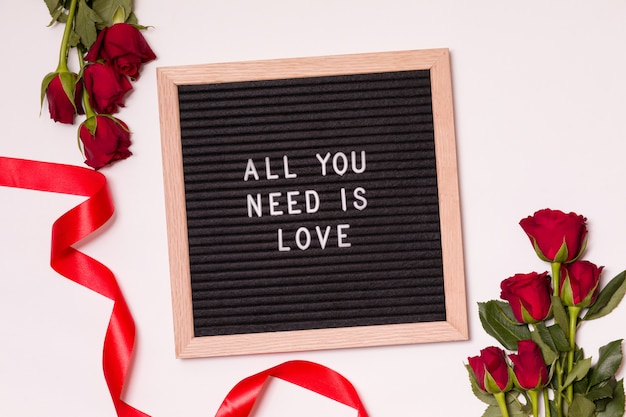 All you need is love - valentines day qoute on letter board with red roses and ribbon.