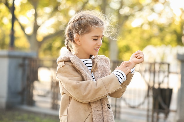 Аллергическая маленькая девочка, царапающая себя на открытом воздухе