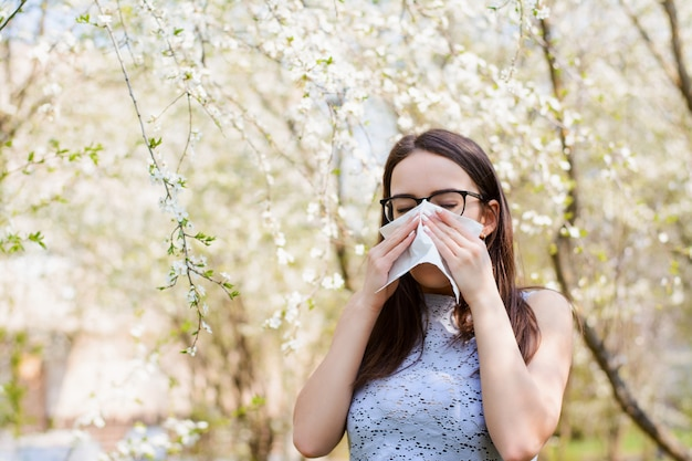 Allergic woman blowing her nose against blooming trees