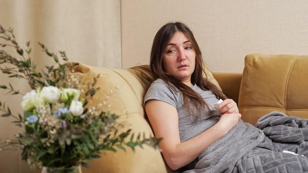 アレルギーの女性が白い紙ナプキンでくしゃみをする