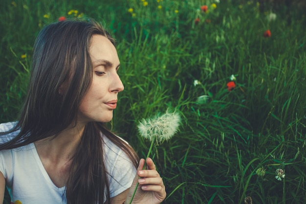 Allergy free concept. woman blowing dandelion