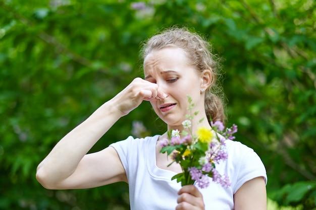 Аллергия. женщина сжала нос рукой, чтобы не чихать от пыльцы цветов