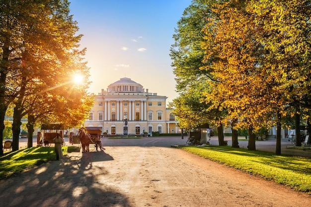 Аллея дворца в павловске, пригороде петербурга, и карета с лошадью осенним солнечным вечером.
