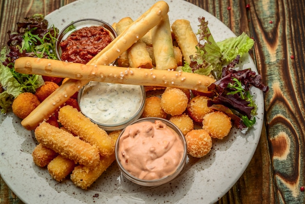 Allsorts of fried snacks with two different sauces on black background