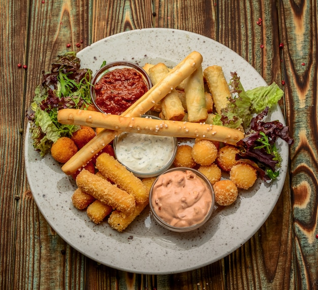 Allsorts of fried snacks with two different sauces on black