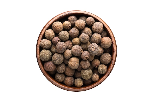Allspice spice in wooden bowl, isolated on white wall. seasoning top view
