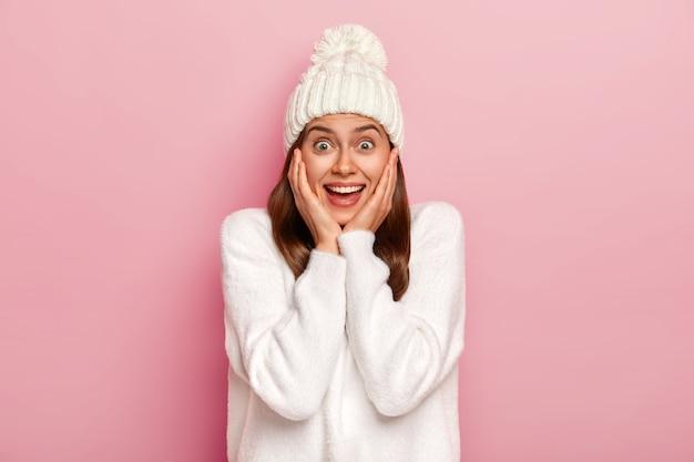 魅惑的な美しいブルネットの女性は、楽しませて明るい感じ、頬に優しく触れ、熱狂的な視線を持ち、白い暖かい帽子と特大のセーターを着ています