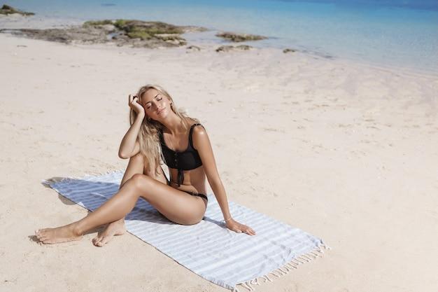 魅惑的な金髪のリラックスした日焼けした女性は、夏に日光浴を楽しんでいます。